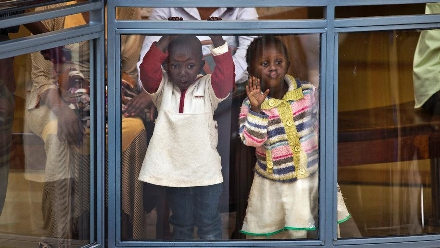 Two Kenyan children look out from an upper level in the reopened Westgate Shopping Mall, nearly two years after a terrorist attack there left at least 67 people dead, in the capital Nairobi, Kenya Saturday, July 18, 2015. Hundreds of shoppers thronged through the reopened mall Saturday, following two years of repairs after security forces battled four gunmen from Somalia's al-Qaida-linked al-Shabab militant group there in September 2013. (AP Photo/Ben Curtis)