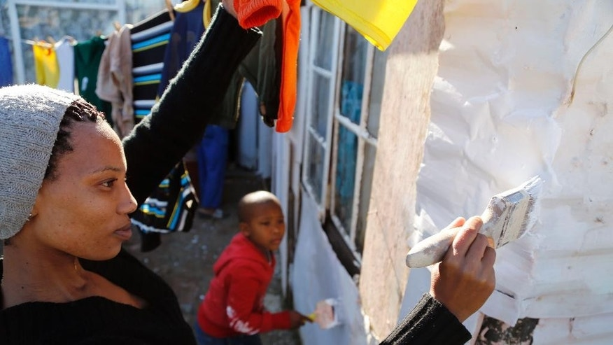 A woman paints a shack with white fire retardant paint as a contribution to International Nelson Mandela day celebrating former South African president Mandela birth day in the township of  Nomzamo, South Africa,  Saturday, July 18, 2015. Thousands of South Africans celebrating former South African president Nelson Mandela birth day by giving  67 minutes of their time to help other people. (AP Photo/Schalk van Zuydam)