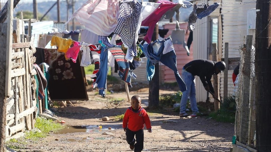 A child walk on a dirt road near his home as people nearby paint shacks with white fire retardant paint as part of their contribution to International Nelson Mandela day celebrating former South African president Mandela birth day in the township of  Nomzamo , South Africa,  Saturday, July 18, 2015. Thousands of South Africans celebrating former South African president Nelson Mandela birthday by giving 67 minutes of their time to help other people. (AP Photo/Schalk van Zuydam)