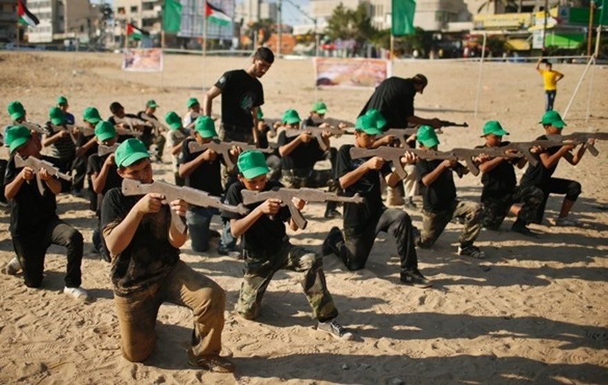 Palestinian boy Mahmoud Haniyeh (front, 1st L), 13, aims a wooden gun during a military-style exercise at a summer camp organized by the Hamas movement in Gaza City June 17, 2013. Tens of thousands of children from the Gaza Strip spend at least part of their holidays in special summer camps, arranged around a wide array of activities. Some, organised by the United Nations, offer sports, art and dance classes. Others, laid on by Gaza's Islamist rulers Hamas, include fun and games, while seeking to reinforce religious values and awareness of the conflict with Israel. Picture taken June 17, 2013. REUTERS/Mohammed Salem (GAZA - Tags: POLITICS EDUCATION SOCIETY)