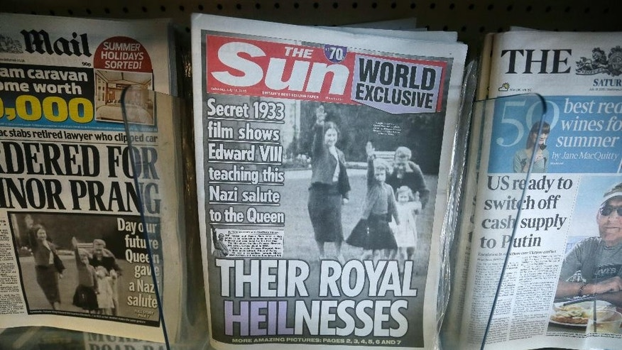 A row of newspapers on display including a paper with a photo of Britain's Queen Elizabeth as a child giving a Nazi salute,  in a shop, in London, Saturday July 18, 2015. Buckingham Palace has expressed its disappointment with a tabloid newspaper for publishing images of a young Queen Elizabeth II performing a Nazi salute together with her family in 1933, the year Adolf Hitler came to power. The palace took the unusual step of commenting on Saturday's report in The Sun newspaper, which shows the queen — then about 7 years old — at the family home in Balmoral, surrounded by her uncle, mother, and sister. The grainy footage also shows Elizabeth's mother making the salute. (AP Photo/Tim Ireland)