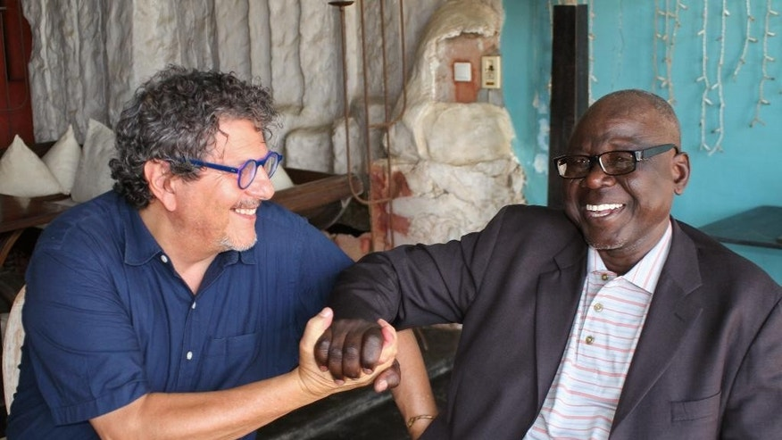 In this photo taken on Monday, July 13, 2015, Reed Brody, a researcher for the New-York-based rights group Human Rights Watch, left, interacts with Souleymane Guengueng, a Chad prisoner from 1987-1990, during an interview with the Associated Press in  Dakar, Senegal. The bodies came daily. Sometimes 10, sometimes 20 lives lost to torture, malnutrition or sickness in prison in Chad, say survivors. The court prosecutor says 2,500 victims have registered as civil parties, and 100 will be called to testify during the trial that will last months. Souleymane Guengueng, a prisoner from 1987-1990 and founder of the victims' association has been anticipating this trial for 25 years. (AP Photo/Carley Petesch)