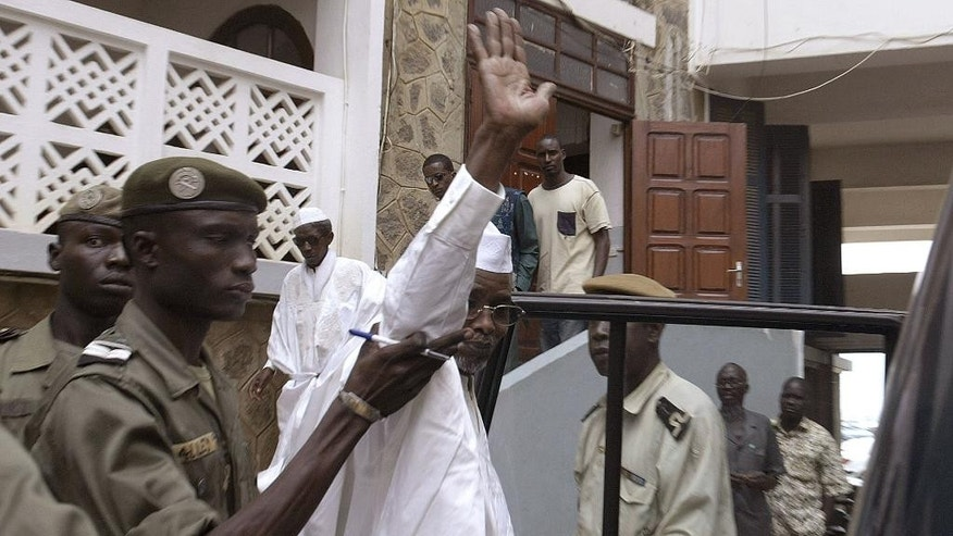 FILE - In this Tuesday, Nov. 15, 2005, file photo, former Chad dictator Hissene Habre, center, waves to reporters as he is led into a car to be taken back to jail following a preliminary court hearing in Dakar, Senegal. Monday, July 20, 2015,  Habre will go on trial in Senegal, fulfilling the work of many who say they suffered abuse under his rule. For more than a decade after his overthrow Habre lived freely in Senegal. His easy exile was a symbol of impunity in Africa, living in luxury under house arrest in 2005 until his arrest in 2013. Now his trial is a warning to other African dictators that they may be held accountable in Africa for their actions, say human rights experts.  (AP Photo/Rebecca Blackwell, File)