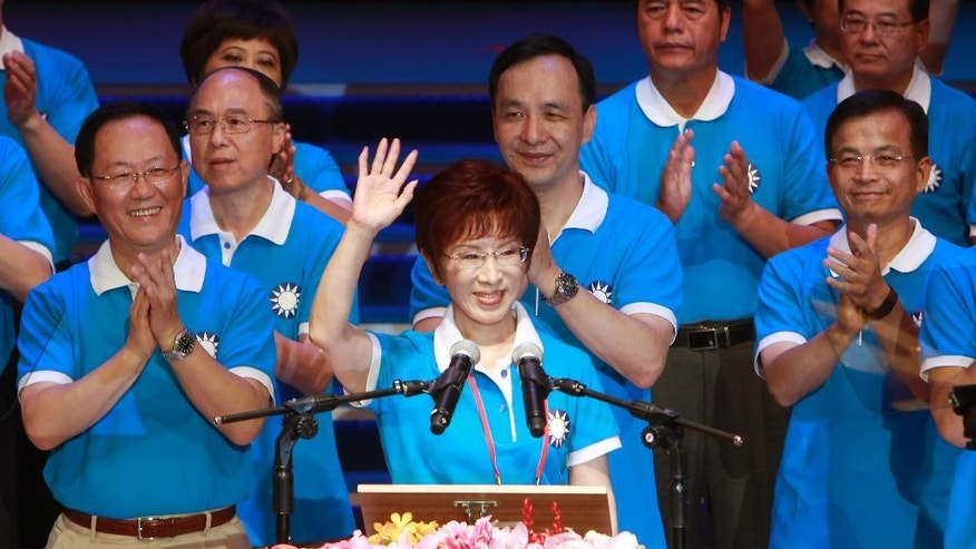 Backed by the ruling Nationalist Party members, Hung Hsiu-chu, a former teacher and current deputy legislative speaker, waves as she is nominated as the party's candidate in the January presidential election, Sunday, July 19, 2015, in Taipei, Taiwan. The top two political parties in Taiwan have each nominated a woman for president in 2016, a historic first signaling acceptance of female leadership and kicking off a campaign highlighted so far by clashing views on ties with political rival China. Hung supportive of friendly relations with China will run against Tsai Ing-wen, the opposition Democratic Progressive Party chairwoman and an advocate of more cautious relations with Beijing. (AP Photo/Chiang Ying-ying)