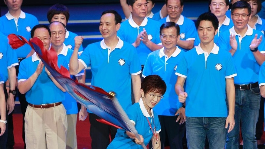 Backed by the ruling Nationalist Party members, Hung Hsiu-chu, a former teacher and current deputy legislative speaker, waves a flag as she is nominated as the party's candidate in the January presidential election, Sunday, July 19, 2015, in Taipei, Taiwan. The top two political parties in Taiwan have each nominated a woman for president in 2016, a historic first signaling acceptance of female leadership and kicking off a campaign highlighted so far by clashing views on ties with political rival China. Hung supportive of friendly relations with China will run against Tsai Ing-wen, the opposition Democratic Progressive Party chairwoman and an advocate of more cautious relations with Beijing. (AP Photo/Chiang Ying-ying)