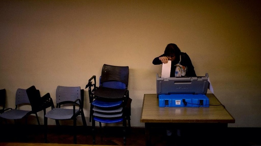 A woman uses an electronic voting machine during the mayoral run-off election in Buenos Aires, Argentina, Sunday, July 19, 2015. With Buenos Aires' voters accounting for nearly 8 percent of Argentina's voting population, its election is closely watched for tendencies for the presidential primaries and the Oct. 25 national election. (AP Photo/Natacha Pisarenko)