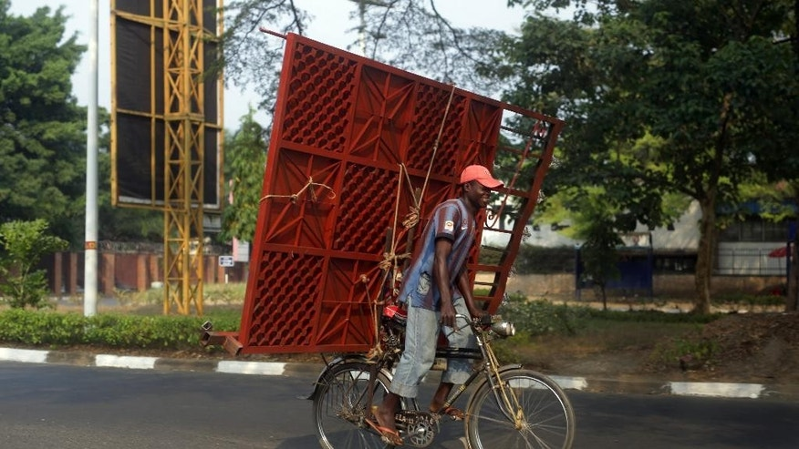 A cyclist carries a metal gate on the back of his bicycle in Bujumbura, Burundi, Sunday July 19, 2015. As Burundians are getting ready to go to the poll Tuesday July 21, three candidates, including two former presidents, announced their withdrawal from Burundi's upcoming presidential race, predicting the contest in this restive African nation will not be free and fair. (AP Photo/Jerome Delay)