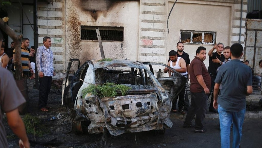 CORRECTS PHOTOGRAPHER'S NAME TO HASSAN MAHMOUD - Palestinians stand around a vehicle destroyed in blast in Gaza City on Sunday, July 19, 2015. At least four explosions rocked Gaza City early Sunday, targeting vehicles belonging to officials from Islamic factions, including the territory's Hamas rulers. There was no claim of responsibility, but speculation immediately centered on supporters of the Islamic State group, who have been battling with Hamas and other Islamic groups in the small coastal strip. (AP Photo/Hassan Mahmoud)