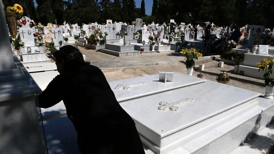 A woman lights a candle on a grave at a cemetery in Athens, Friday, July 17, 2015. Funeral homes here are struggling to cope with banking restrictions _ with a modest funeral costing more the 15 times the daily ATM withdrawal limit _ in a country that traditionally carries out funerals shortly after death and almost everything is paid for in cash. (AP Photo/Petros Karadjias)