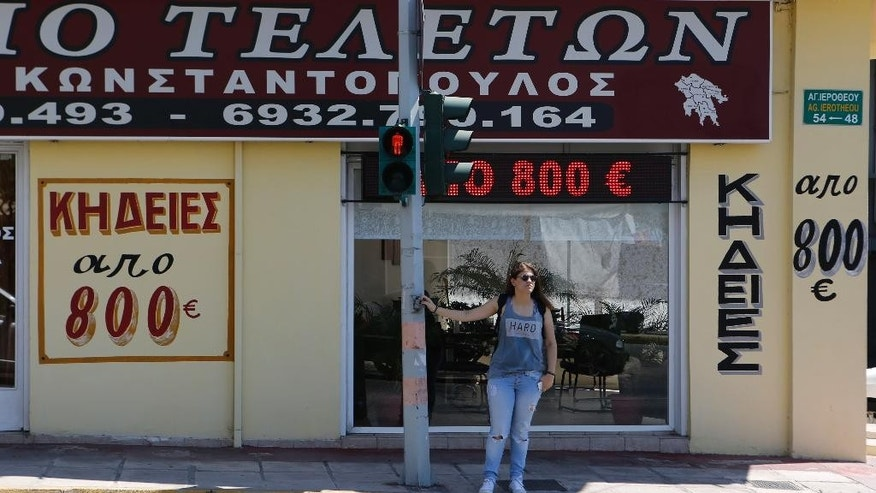 "A pedestrian waits at a traffic light as the signs outside a funeral home reading ""Funerals from 800 euros'' in Athens, Friday, July 17, 2015. Funeral homes here are struggling to cope with banking restrictions _ with a modest funeral costing more the 15 times the daily ATM withdrawal limit _ in a country that traditionally carries out funerals shortly after death and almost everything is paid for in cash. (AP Photo/Petros Karadjias)"