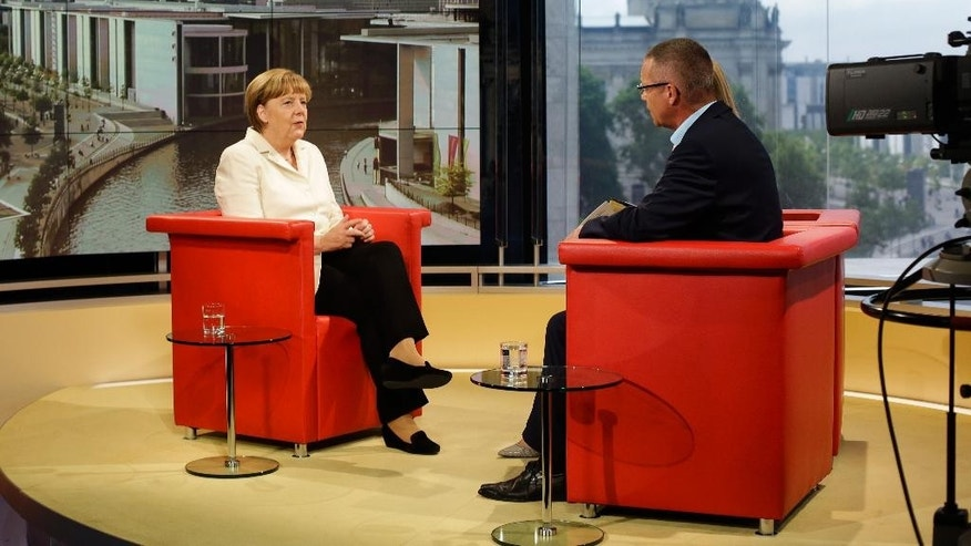 German Chancellor Angela Merkel, left, talks with journalists Reinald Becker, right, and Tina Hassel, hidden, prior to  an  interview at the studios of German public broadcaster ARD  in Berlin, Germany, Sunday, July 19, 2015. (AP Photo/Markus Schreiber)