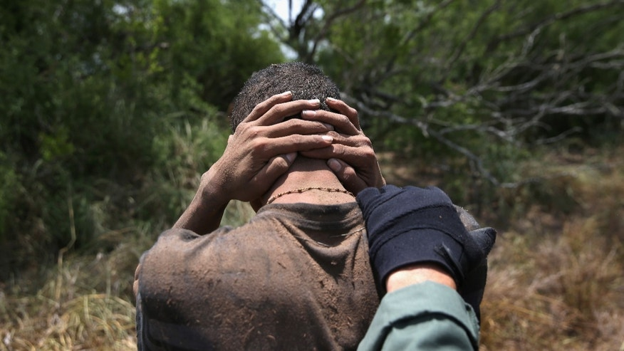 U.S. Border Patrol agents detain undocumented immigrants on July 23, 2014 near Falfurrias, Texas.
