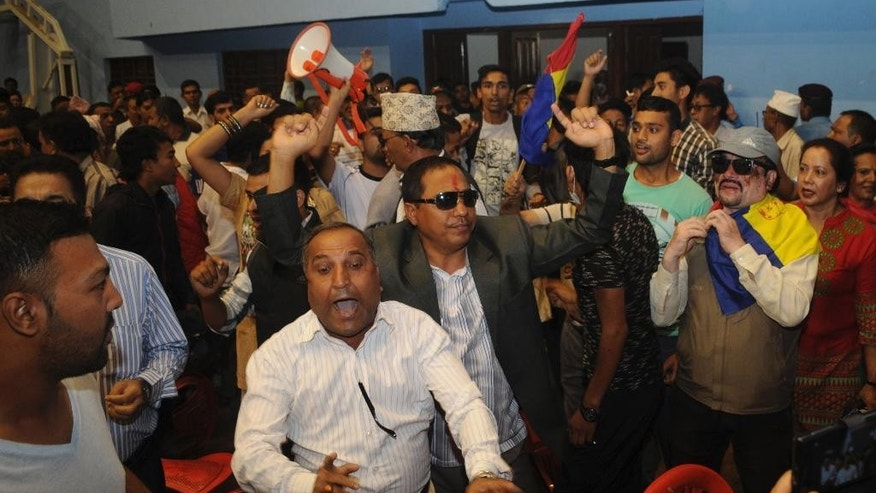 Protestors from Rastriya Prajatantra Party Nepal shout slogans after storming into the national stadium where Deputy Prime Minister Prakash Man Singh was collecting suggestions on a draft constitution in Kathmandu, Nepal, Monday, July 20, 2015. Protesters demanding that Nepal be turned back into a Hindu nation scuffled with police Monday and threw chairs at the country's deputy prime minister. (AP Photo/ Dipesh Shreshta)