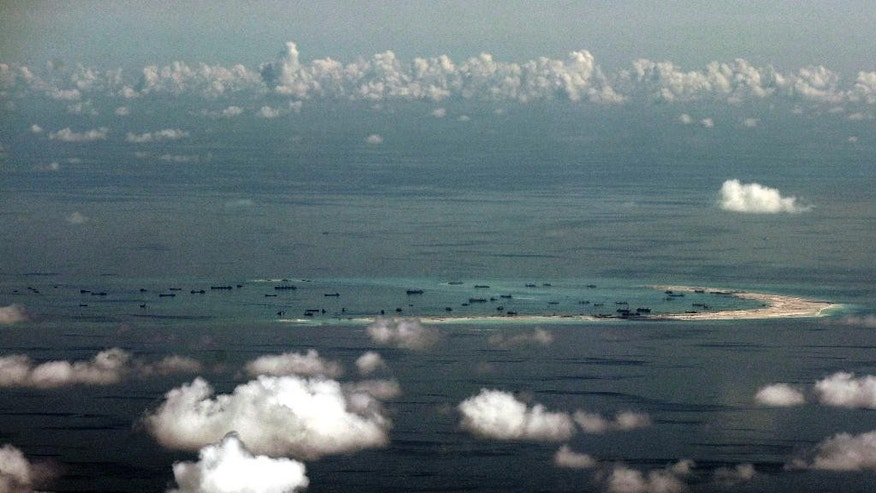FILE - This aerial file photo taken May 11, 2015 through a glass window of a military plane shows China's alleged on-going reclamation of Mischief Reef in the Spratly Islands in the South China Sea. The new U.S. commander of the Pacific Fleet joined a seven-hour surveillance flight over the South China Sea on board one of America's newest spy planes, a move over the weekend that will likely annoy China. Adm. Scott Swift joined the surveillance mission on board a P-8A Poseidon plane on Saturday to witness the aircraft's full range of capabilities, the U.S. Pacific Fleet said Sunday, July 19. (Ritchie B. Tongo/Pool Photo via AP, File)