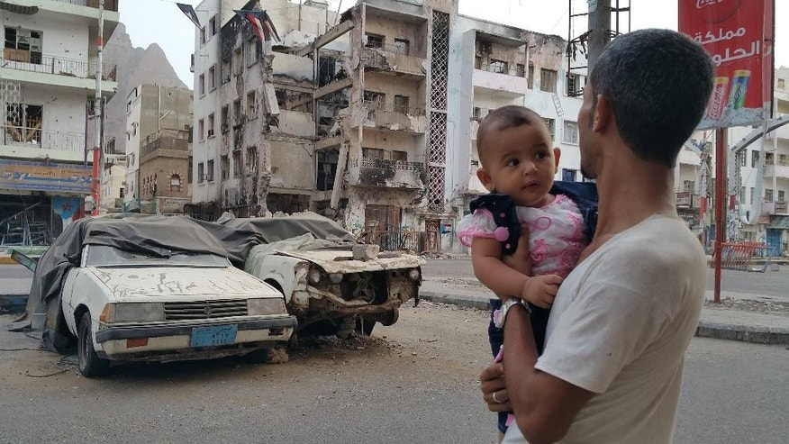 A Yemeni man carrying his daughter looks at a building destroyed during fighting against Houthi fighters in the port city of Aden, Yemen, Sunday, July 19, 2015. Shiite rebels and their allies in Yemen randomly shelled a town Sunday outside of Aden after losing control of some the port city's neighborhoods, killing at least 45 people and wounding 120, officials said. (AP Photo/Ahmed Sameer)