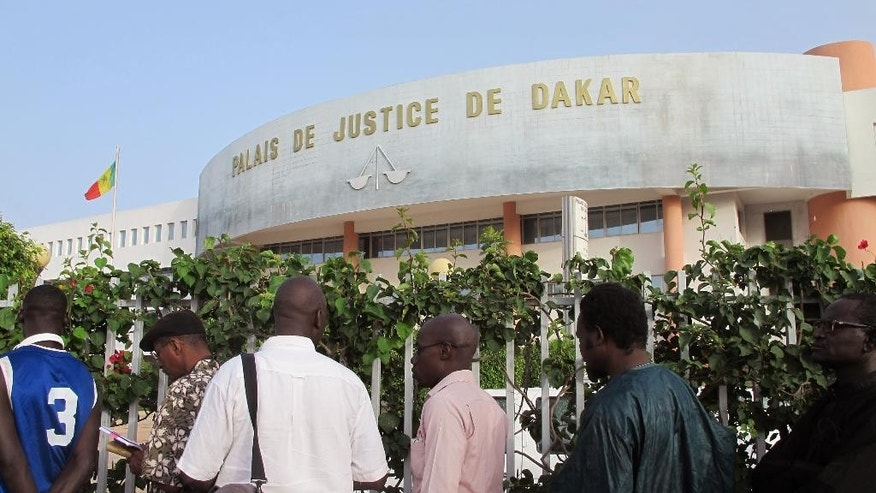 People stand in line before entering the court building, rear, where the trial of former Chadian dictator Hissene Habre is taking place in Dakar, Senegal, Monday, July 20, 2015,  The trial of former Chadian dictator Hissene Habre, accused of overseeing the deaths of thousands, had a chaotic beginning Monday as security forces ushered the ex-leader into and then out of the Senegal courtroom amid protests by his supporters.(AP Photo/Carley Petesch)