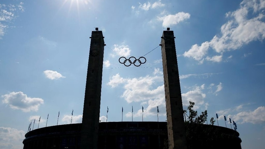 FILE - In this June 6, 2015 file photo the Olympic Rings are silhoetted outside the Olympic stadium in Berlin ahead of the Champions League final soccer match between Juventus Turin and FC Barcelona. Europe's largest Jewish sporting event is coming to Germany for the first time, bringing more than 2,000 Jewish athletes together from around the world to compete at a site constructed by the Nazis for the 1936 Olympics.  (AP Photo/Luca Bruno, file)