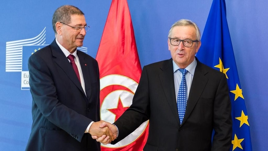 European Commission President Jean-Claude Juncker, right, welcomes Tunisia's Prime Minister Habib Essid upon his arrival at EU headquarters in Brussels on Monday, July 20, 2015. (AP Photo/Geert Vanden Wijngaert)