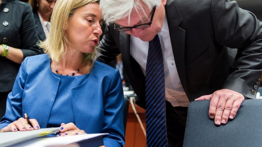 German Foreign Minister Frank-Walter Steinmeier, right, talks with European Union High Representative Federica Mogherini during a meeting of EU foreign minister at the EU Council building in Brussels on Monday July 20, 2015. (AP Photo/Geert Vanden Wijngaert)