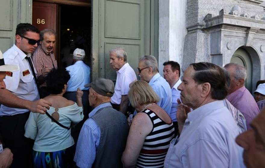 The first customers, most of them pensioners, enter a branch at the National Bank of Greece headquarters in Athens, Monday, July 20, 2015. Greek banks reopen on Monday morning, but many restrictions on transactions, including cash withdrawals, will remain. Also, many goods and services will become more expensive as a result of a rise in Value Added Tax approved by Parliament last Thursday, among the first batch of austerity measures demanded by Greece's creditors. (AP Photo/Thanassis Stavrakis)