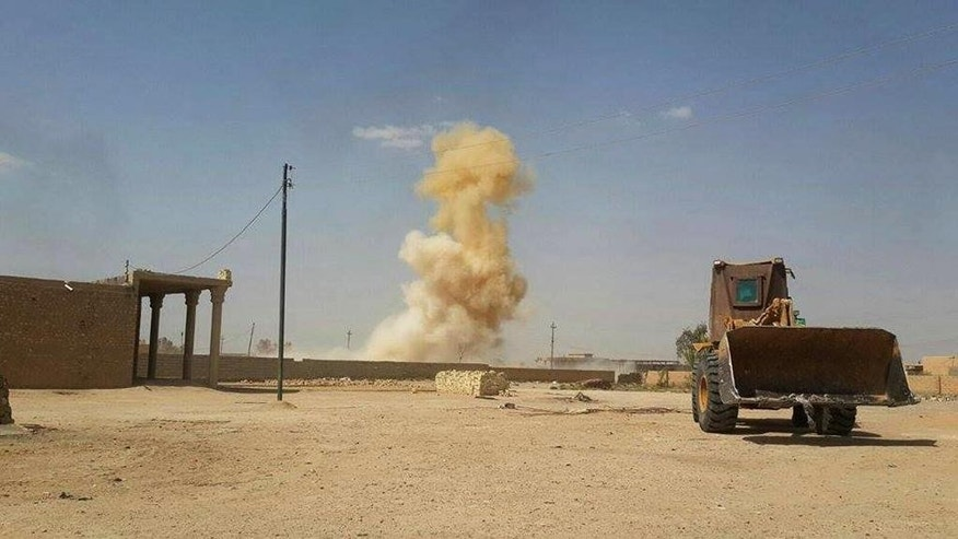 In this Sunday, July 19, 2015 photo, smoke rises following a U.S.-led coalition airstrike against Islamic State group positions as a bulldozer belonging to the Iraqi security forces backed by Shiite and pro-government Sunni fighters is deployed for fighting against Islamic State group militants in Tash district in southern Ramadi, Anbar province, Iraq. The country's security officials said that militants from the Islamic State group blew up a sports stadium near the militant-held city of Ramadi. (AP Photo)