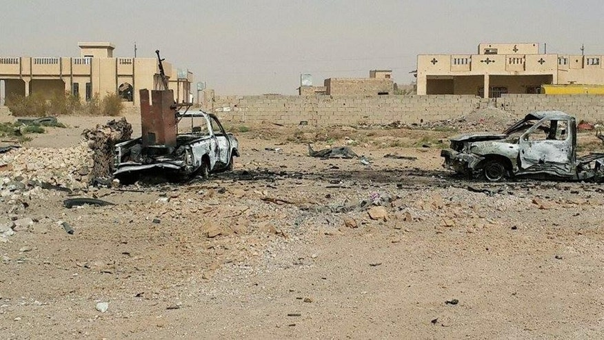 This Sunday, July 19, 2015 photo shows destroyed trucks with weapons belonging to Islamic State group militants following a U.S.-led coalition airstrike against IS positions in Tash district in southern Ramadi, Anbar province, Iraq. The country's security officials said that militants from the Islamic State group blew up a sports stadium near the militant-held city of Ramadi. (AP Photo)