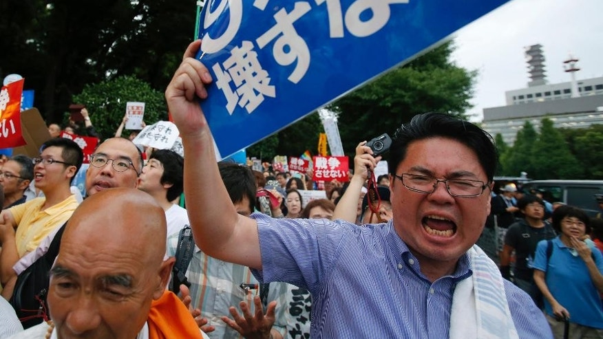 "FILE - In this Thursday, July 16, 2015 file photo, an anti-war protester yells while waving a sign that reads: ""Don't destroy Article 9 of the constitution"" during a rally after Japan's lower house of parliament approved legislation that would expand the role of the nation's military, outside the Parliament building in Tokyo. Japan emphasized China as a threat in escalating regional tensions in this year's annual defense report, approved Tuesday, July 21 by the Cabinet, as Prime Minister Shinzo Abe's government tries to convince the public of the need to pass legislation to give Japan's military a greater role. (AP Photo/Shuji Kajiyama, File)"