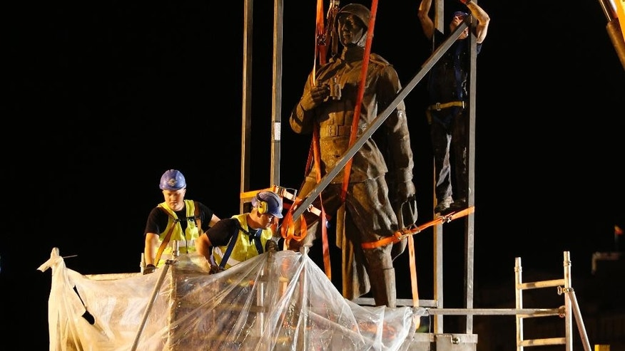 Workers prepare to dismantle Soviet era statues from the Green Bridge over the Neris river in Vilnius, Lithuania, Monday, July 20, 2015. Statues depicting Red Army soldiers, workers, students and peasants were erected on the historic Green Bridge over the River Neris in 1952, 12 years after the Soviet Union occupied Lithuania and its Baltic neighbors, Latvia and Estonia. (AP Photo/Mindaugas Kulbis)