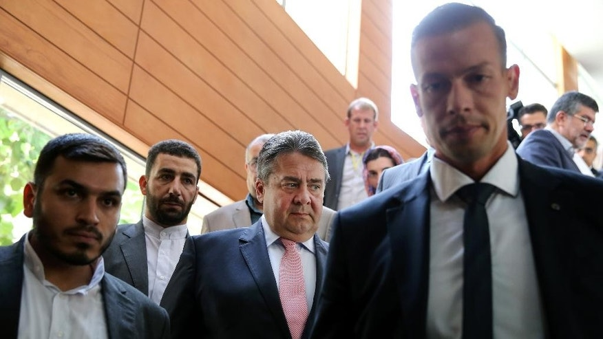 German Vice Chancellor and Economy Minister Sigmar Gabriel, center, makes his way to a conference after a round of talks with Iranian Oil Minister Bijan Zanganeh in Tehran, Iran, Monday, July 20, 2015. (AP Photo/Ebrahim Noroozi)