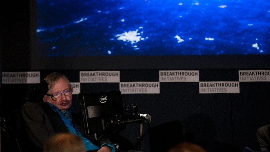 "Renowned physicist Stephen Hawking sits in front of a presentation image during a press conference in London, Monday, July 20, 2015.  Renowned physicist Stephen Hawking and Russian tech entrepreneur Yuri Milner are pushing the search for extraterrestrial life into higher gear. The pair said Monday the $100 million ""Breakthrough Initiatives"" program funded by Milner will harness computer power as never before in a search of the heavens.  (AP Photo/Matt Dunham)"