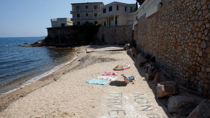"In this photo dated Friday July 17, 2015 a  view of the public beach called ""La Mirandole"" located below a mansion owned by the Saudi royal family in Golfe Juan Vallauris, southern France. Last week, angry beachgoers won a temporary halt to unauthorized work ahead of the royal visit, notably a cement slab on the sand for an elevator allowing direct beach access from the mansion. Sign on beach reads : No to construction works. (AP Photo/Claude Paris)"