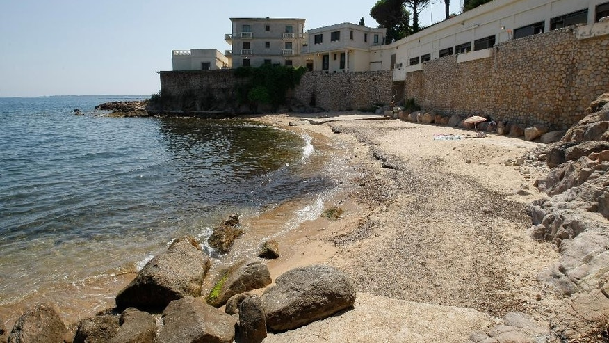"In this photo dated Friday July 17, 2015 a  view of the public beach called ""La Mirandole"" located below a mansion owned by the Saudi royal family in Golfe Juan Vallauris, southern France. Last week, angry beachgoers won a temporary halt to unauthorized work ahead of the royal visit, notably a cement slab on the sand for an elevator allowing direct beach access from the mansion.  (AP Photo/Claude Paris)"