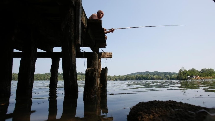 A man sits in shade as he fishes in  a lake near Tuzla, 120 kms north of Sarajevo, Monday, July, 20 ,2015. A heat wave has hit Bosnia and surrounding regions with the temperature reaching 40 Celsius (104 Fahrenheit).   (AP Photo/Amel Emric)