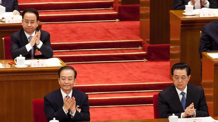 FILE - In this Sunday, March 11, 2012 file photo, Ling Jihua, top left, a loyal aide and confidante to President Hu Jintao, bottom right, sits behind Premier Wen Jiabao, bottom left, and Hu as they attend a plenary session of the National People's Congress at the Great Hall of the People in Beijing. China's state media say former President Hu Jintao's top aide has been stripped of his party membership, removed from all government positions, and will be criminally prosecuted on corruption charges. The official Xinhua News Agency said Monday, July 20, 2015 that an internal investigation found that Ling, who once served as head of the Communist Party's general office, took huge bribes and used his position to seek benefits for others. (AP Photo/Andy Wong, File)