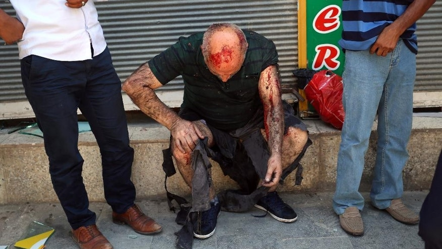 A wounded man waits for medical attention shortly after an explosion in the southeastern Turkish city of Suruc near the Syrian border, Turkey, Monday, July 20, 2015, An explosion Monday killed at least 10 people and injured scores of others in the southeastern Turkish city of Suruc near the Syrian border, state-run Turkish news agencies reported. The private Turkish DHA news agency said at least 50 people had been hospitalized in the midday explosion. There was no immediate claim of responsibility for the blast. (AP Photo/Ozcan Soysal ) TURKEY OUT