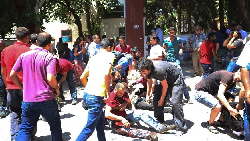 People help the wounded after an explosion in the southeastern Turkish city of Suruc near the Syrian border, Turkey, Monday, July 20, 2015. An explosion Monday killed at least 10 people and injured scores of others in the southeastern Turkish city of Suruc near the Syrian border, state-run Turkish news agencies reported. The private Turkish DHA news agency said at least 50 people had been hospitalized in the midday explosion. There was no immediate claim of responsibility for the blast. (AP Photo/Ozcan Soysal ) TURKEY OUT