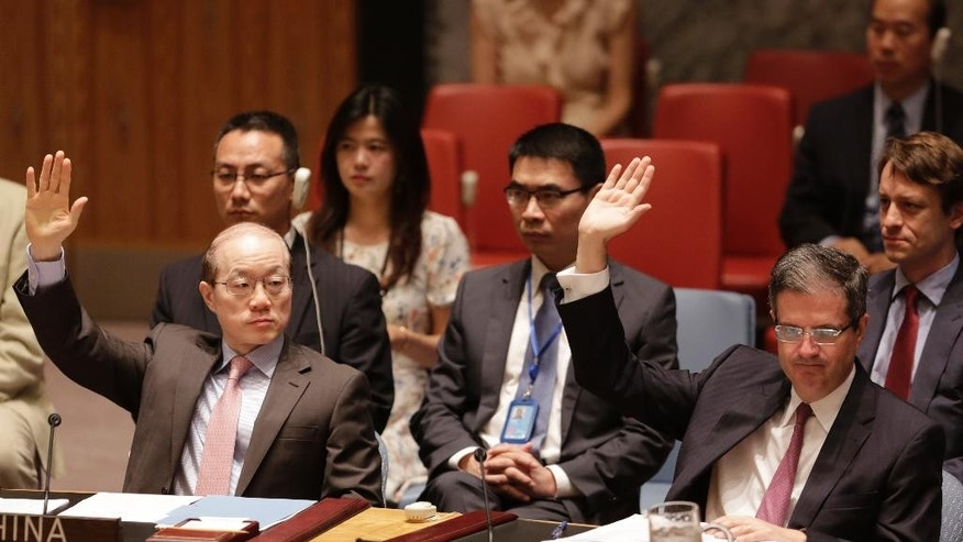 China's United Nations Ambassador Liu Jieyi, left, and French Ambassador Francois Delattre vote in favor of a Security Council resolution approving Iran's nuclear deal at United Nations headquarters, Monday, July 20, 2015. (AP Photo/Mark Lennihan)