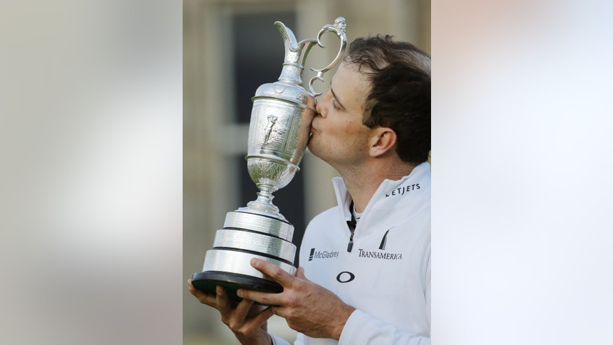 United States' Zach Johnson kisses the trophy as he poses for photographers after winning a playoff after the final round at the British Open Golf Championship at the Old Course, St. Andrews, Scotland, Monday, July 20, 2015. (AP Photo/David J. Phillip)