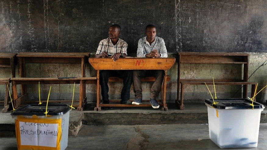 Election observers sit in an empty polling station for the presidential elections in Bujumbura, Burundi, Tuesday, July 21, 2015. A low turnout was experienced in several polling stations in the Burundi's capital at the start of voting in the country's presidential election following a night of explosions and gunfire in at least two opposition strongholds that oppose President Pierre Nkurunziza's candidacy for a third term in office. (AP Photo/Jerome Delay)