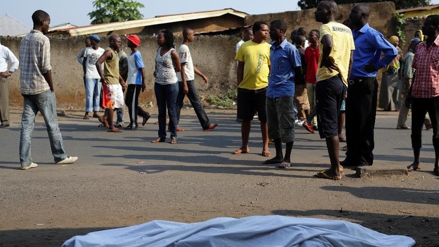 The body of a man killed overnight is laid on a street in Bujumbura, Burundi as polls open for the presidential elections Tuesday July 21, 2015. A low turnout was experienced in several polling stations in the Burundi's capital at the start of voting in the country's presidential election following a night of explosions and gunfire in at least two opposition strongholds that oppose President Pierre Nkurunziza's candidacy for a third term in office. (AP Photo/Jerome Delay)