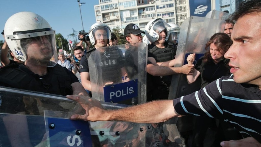 Turkish police in riot gear, left, clash with protesters in Istanbul, Tuesday, July 21, 2015, that tried to stage a march to denounce the deaths of a Monday explosion in the Turkish town of Suruc near the Syrian border. Authorities suspected the Islamic State group was behind an apparent suicide bombing Monday in Suruc in southeastern Turkey that killed 31 people and wounded nearly 100 — a development that could represent a major expansion by the extremists at a time when the government is stepping up efforts against them. (AP Photo/Lefteris Pitarakis)