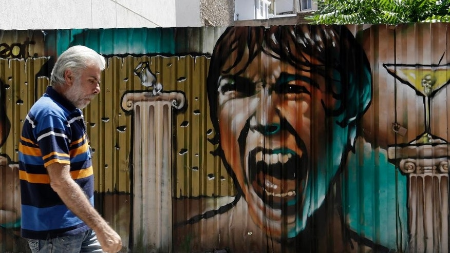 A man passes graffiti in Athens, Tuesday, July 21, 2015. Banks reopened Monday for the first time in three weeks. But for most Greeks, already buffeted by six years of recession, Monday was all about rising prices as tax hikes demanded by creditors took effect. (AP Photo/Thanassis Stavrakis)