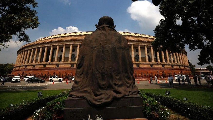 A statue of Mahatma Gandhi overlooks the Indian Parliament house on the opening day of its monsoon session, in New Delhi, India, Tuesday, July 21, 2015. (AP Photo/ Manish Swarup)