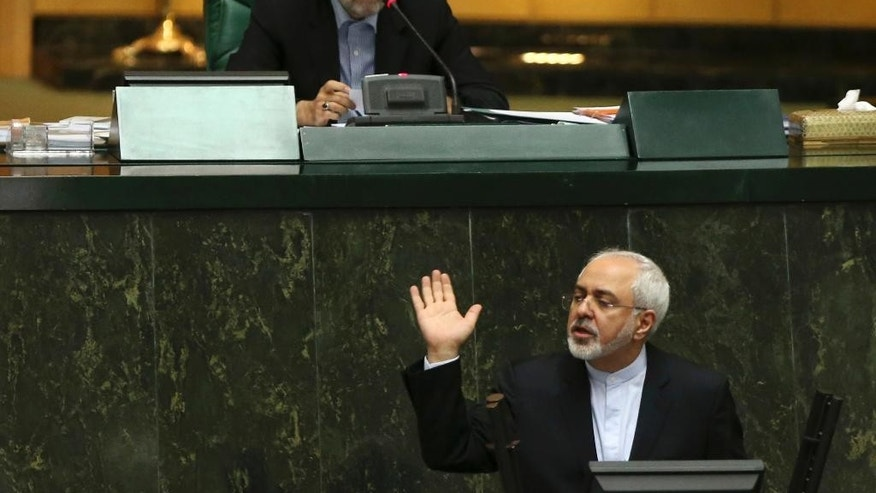 Iranian Foreign Minister Mohammad Javad Zarif, bottom, who is also Iran's top nuclear negotiator, addresses parliament while speaker Ali Larijani sits above, in an open session of parliament in Tehran, Iran, Tuesday, July 21, 2015. Iran's foreign minister has handed over the landmark nuclear deal reached with world powers last week to the country's parliament so that Iranian lawmakers can review it, state media said Tuesday. (AP Photo/Vahid Salemi)