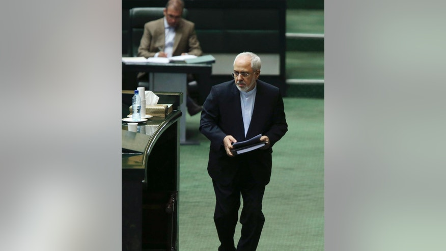Iranian Foreign Minister Mohammad Javad Zarif, who is also Iran's top nuclear negotiator, arrives at podium in an open session of parliament in Tehran, Iran, Tuesday, July 21, 2015. Iran's foreign minister has handed over the landmark nuclear deal reached with world powers last week to the country's parliament so that Iranian lawmakers can review it, state media said Tuesday. (AP Photo/Vahid Salemi)