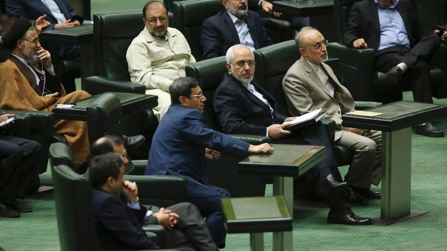 Iranian Foreign Minister Mohammad Javad Zarif, center right, who is also Iran's top nuclear negotiator, and chief of Iran's Atomic Energy Organization Ali Akbar Salehi, right, listen to a speaker in an open session of parliament in Tehran, Iran, Tuesday, July 21, 2015. Iran's foreign minister has handed over the landmark nuclear deal reached with world powers last week to the country's parliament so that Iranian lawmakers can review it, state media said Tuesday. (AP Photo/Vahid Salemi)