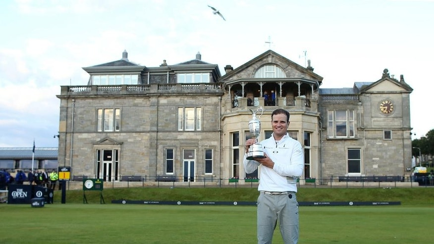 United States' Zach Johnson poses with the trophy after winning a playoff after the final round at the British Open Golf Championship at the Old Course, St. Andrews, Scotland, Monday, July 20, 2015.  (AP Photo/Peter Morrison)