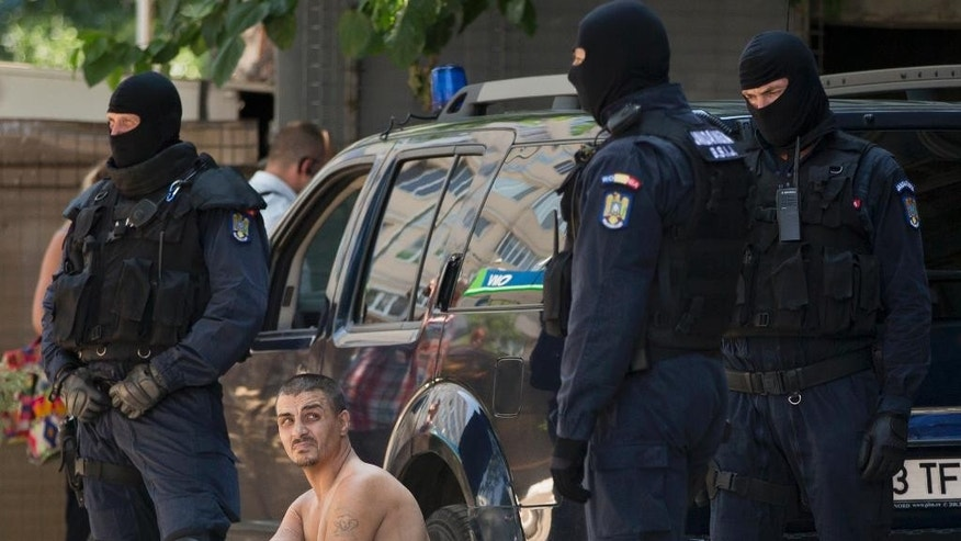 Florin Hora, known as Bruce Lee, a leader of the homeless people inhabiting the sewers and suspected ringleader of a drug trafficking network, watches special police officers as he sits handcuffed near the main railway station during a police raid in Bucharest, Romania, Tuesday, July 21, 2015. Police in Romania have searched the capital's sewers in an anti-drug raid and detained dozens of people, mostly homeless, including the suspected ringleader, for questioning on suspicion of trafficking.(AP Photo/Vadim Ghirda)