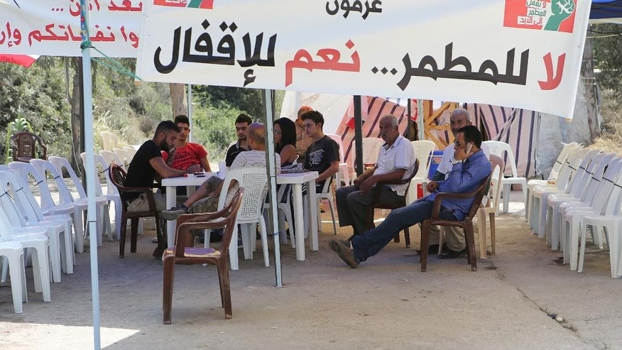 "Lebanese protesters sit under a tent as part of their sit, as they close the entrance of the largest landfill, in the coastal town of Naameh, south of Beirut, Lebanon, Tuesday, July 21, 2015. Garbage began to pile up on the streets of Beirut on Tuesday after the main trash collecting company stopped picking it up after residents of areas south of the capital closed the road leading to Lebanon's largest landfill. The Arabic banner reads:""The Social Cultural Association, Aramoun, No to the landfill, Yes to closing it. (AP Photo/Hussein Malla)"