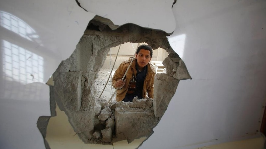 "A boy looks through a hole in a classroom of a school damaged by Saudi-led airstrikes in Sanaa, Yemen, Monday, July 20, 2015. The death toll in Yemen from the Shiite rebel shelling of a town near the southern port city of Aden rose on Monday to nearly 100, the head of an international aid group said, describing it as ""the worst day"" for the city and its surroundings in over three months of fighting. (AP Photo/Hani Mohammed)"